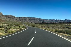 Road though scrubland leading to mountains. Lonesome road though scrubland leading to mountains, bushes are growing on lava minerals Royalty Free Stock Image