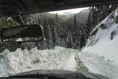 Road thru forest in mountains full of snow in a winter time Royalty Free Stock Photos