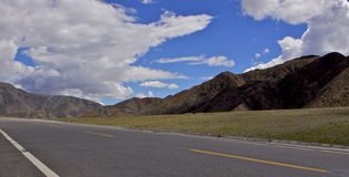 Road in Tibet. Blue skies and white clouds over Tibetan Road Stock Images