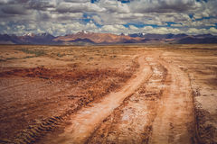 Road through the Tibetan plateau. Muddy and clay mountain road through the high central Tibetan plateau, Tibet, China Royalty Free Stock Images