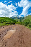 Road with tire tracks leading to mountains and Stock Photo