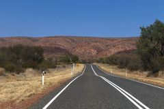 On the road to Alice Springs, Australia. Road extending into the distance, between bushes growing from the red earth stock image