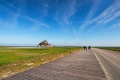 Road to amazing Mont Saint Michel abbey. Landscape photo during sunrise. Normandy, France. Road to amazing Mont Saint Michel abbey. Tourists are going to the Stock Photos