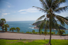 The road to the background of the sea and mountains . The road passing through a picturesque area of Thailand . Palm trees , sea and mountains stock photography
