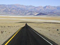 Road to Badwater. Single lane desert road descending into valley with salt flats and mountains in the distance royalty free stock images