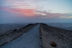 Road to beautiful infifnite sunrise over holy land in Israe. L. Magic judean desert nature with mountains, clouds, red sun and old ruins. Landscape with nobody Stock Image