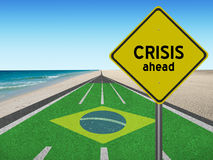 Road to Brazil olympic games in Rio with sign Crisis ahead. Running track with word Crisis ahead leading to Rio de Janeiro, Brazil at the beach Stock Photos