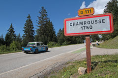 On the road to Chamrousse. CHAMROUSSE, FRANCE, August 20, 2015 : Historic racing car goes to the start of uphill race and leaves the mountain resort of Royalty Free Stock Image