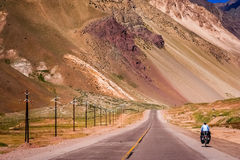 On the road to Chile. Woman cycling on the empty road from Mendoza in Argentina to Valparaiso in Chile, climbing constantly to the border and passing Park Royalty Free Stock Photography
