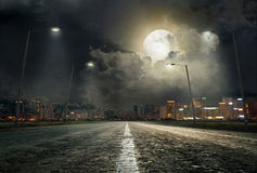 The road to the city 2. Asphalt road leading into the city at night royalty free stock photo