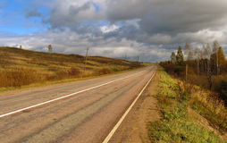 Road to clouds. Country road on a background of autumn landscape in Russia royalty free stock images