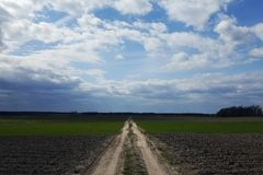 Road to the clouds, passes through a plowed field. The road to the clouds, passes through a plowed field. The Ukrainian Plains Royalty Free Stock Images