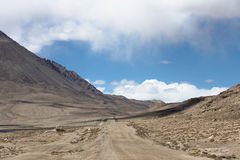 Road to clouds in valley in the foothills of the Fann mountains. Stock Photo