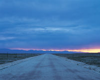 Road to dawn. A road straight ahead to dawn. there is a gleam of coming sunrise on the ridge Stock Image