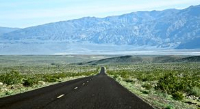 Road to Death Valley. Long black straight two lane road leads you down hill toward the mountains surrounding Death Valley California Stock Photography
