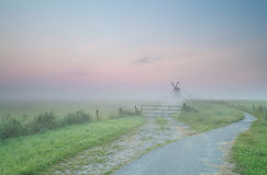 Road to Dutch windmill in morning fog Royalty Free Stock Images