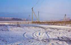 Road to the edge of village.Snow-covered field and distant woods. Royalty Free Stock Photography