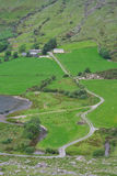 Road to farm in countryside. High angle view of winding road leading to farm in countryside, Ireland stock photography
