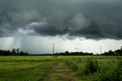 The road to the field with the rain clouds are falling.  Stock Images