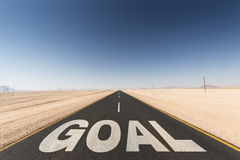 Road to goal. Black asphalt road in the desert leading to the  goal. Business concept for success and motivation Royalty Free Stock Photo