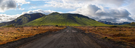 Road to green volcano, Landmannalaugar, Iceland. Panoramic, vanishing point view of dirt road leading straight from the foreground up to the base of green, moss Stock Photos