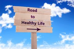 Road to healthy life. Wooden sign with blue sky background Stock Photos
