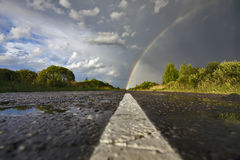 The road to heaven. The road goes to horizont there we can see a rainbow Royalty Free Stock Image