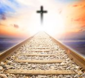 Road to heaven. Railway leading to the cross at sunset background stock images