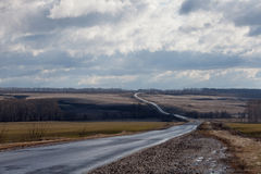 The road to the horizon. Road among the fields early in the spring stretches to the horizon Royalty Free Stock Image