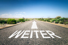 Road to horizon. An image of a road to the horizon with text next in german language Stock Photos