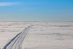 The road to the horizon in snowy wilderness Stock Images