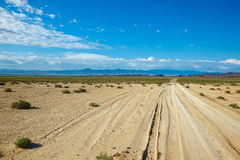 Road to infinity. Dry road through steppe in far mountains in bright day Royalty Free Stock Photography