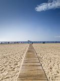 Road to the Island. Wooden walkway on the sand of a beach leading to the coast, with an island on the horizon Royalty Free Stock Photos