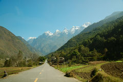 Road to jade dragon mountain. Road and jade dragon mountain at the end Stock Photo