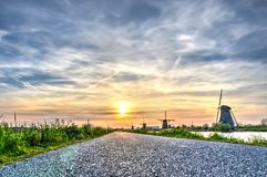 The road to Kinderdijk. Low view of a narrow asphalt road leading to the famous windmills at Kinderdijk Unesco world heritage site, under a scenic sunset sky Stock Photo