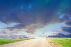 Road to the light. A scenic road leading towards a distant light Royalty Free Stock Images