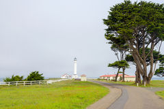 The road to the lighthouse on the shores of the Pacific Ocean Royalty Free Stock Images