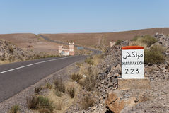 Road to Marrakech. Milestone indicating Marrakech in a desertic area of Morocco Royalty Free Stock Photography
