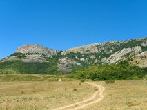 Road to mountains. Road in meadow to mountains Royalty Free Stock Photography