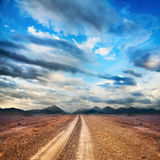 Road to the mountains. Through the desert at sky with clouds Stock Photo