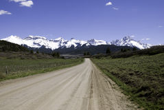 Road to Mountains. Unpaved, dirt road to snowy mountains in western Colorado Royalty Free Stock Images