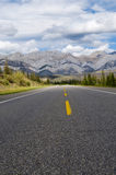 Road to the Mountains. Selective focus on the foreground portion of the road leading to the mountain range Royalty Free Stock Images