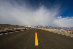 Road to Mountains. With Mysterious Clouds and Blue Sky royalty free stock image