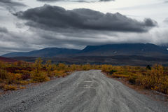 The road to the mountains and a dark cloud over the mountains. Royalty Free Stock Photos