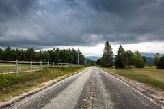 The road to the mountains. Late summer in the Adirondack Mountains in New York with a swampy foreground and fog in the background mountains royalty free stock photo