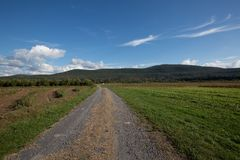 Old dirt road leading to mountains. Road leading to the mountains in upstate New York with clouds Royalty Free Stock Photos