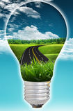 Road to Nature. Light bulb with way to nature on blue sky day Stock Photos