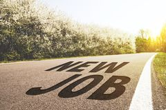 Road to new job. Road in the countryside with flowering trees and New Job written on the asphalt. Backlit view Stock Images