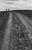 Road to nowhere. Two persons walking on a rural road leading nowhere, remote area near Cluj. Film scan, showing grain royalty free stock image