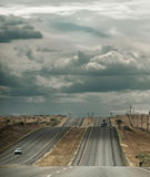 Road to Nowhere. Traffic across the desert under a cloudy sky Royalty Free Stock Images